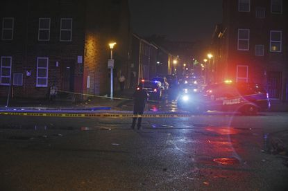 Baltimore City police officers block off the scene of a shooting last fall.