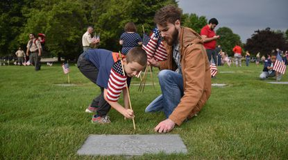 Max Hardy, 7, from Troop 209, places a flag with help from his father Brandon, of Odenton, at the Maryland Veterans Cemetery in Crownsville on the Saturday morning before Memorial Day.