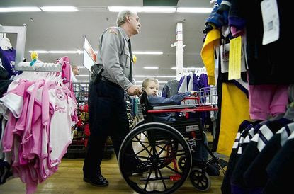 Maj. Ron Stevens pushes Jonathan (who twisted his growth plate) through the Walmart in Westminster during the Dec. 10 Shop with a Cop event.