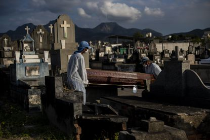 FILE - In this June 18, 2021, file photo, cemetery workers carry the coffin that contains the remains of 89-year-old Irodina Pinto Ribeiro, who died from COVID-19 related complications, at the Inhauma cemetery in Rio de Janeiro, Brazil. The global death toll from COVID-19 has eclipsed 4 million as the crisis increasingly becomes a race between the vaccine and the highly contagious delta variant. (AP Photo/Bruna Prado, File)