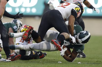 Michigan State's Elijah Collins, right, is stopped by Maryland's Isaiah Davis, left, during the first half of an NCAA college football game, Saturday, Nov. 30, 2019, in East Lansing, Mich. (AP Photo/Al Goldis)