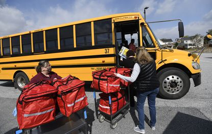 Meals are loaded onto a school bus outside Northwest Middle School in Taneytown Thursday, April 16, 2020. The school system has been sending out meals along bus routes to serve families with children in outlying areas.