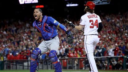 Willson Contreras of the Chicago Cubs celebrates next to Bryce Harper of the Washington Nationals after Harper struck out to end Game 5 of the National League Divisional Series at Nationals Park on Oct. 13, 2017 in Washington, D.C.