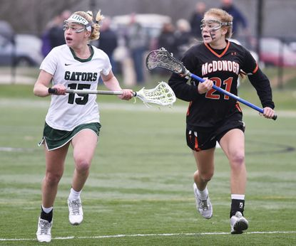 Sisters Paige Aldave (No. 15), of St. Paul's School for Girls, and Andie Aldave (No. 21), of McDonogh, sprint up the field during a girls lacrosse game at St. Pauls School in Brooklandville, Thursday, April 9, 2015.