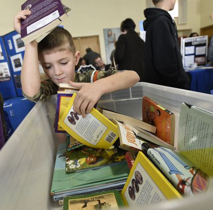 Joseph Hawk, 6, peruses a bin of free books while visiting the Literacy Council of Carroll County's table during Monday's Winter Resource Fair at Westminster United Methodist Church Jan. 29, 2018.