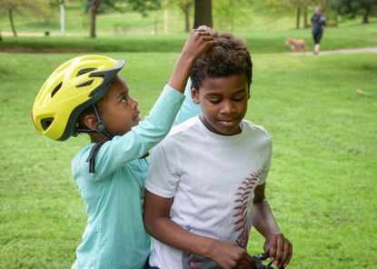 Lydia Wesby, 7, adjusts her 9-year-old brother Mitchell's hair after he took his helmet off in Patterson Park.