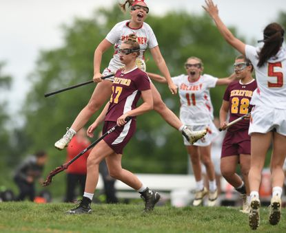 Dulaney's Kaitlyn Dabkowski leaps in the air by a dejected Isabella Peterson, of Hereford, as she celebrates her game-winning goal against Hereford in the Baltimore County girls lacrosse championship game at Dulaney High School on Saturday, May 6.