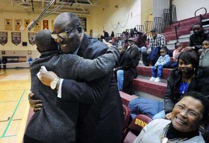 "Coach Bob Wade, center, hugs his former player, Muggsy Bogues, as his wife, Carolyn Wade, smiles during the ceremony in which Dunbar High School named its basketball court ""Coach Wade Court."""