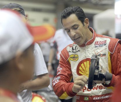 In the paddock area, Helio Castroneves talks with fans and shows them his steering wheel while his mechanics prepare his backup car. Helio was involved in a crash with Tony Kanaan during a practice round of Baltimore's 1st Grand Prix.