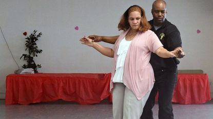 Leonora Pompey, of North Baltimore, receives instruction from Milton Kent, president of Breeze Social Dance Studio, during Baltimore Ceasefire's Urban Dance Event at the Forest Park Senior Center, one of the events taking place as part of a Ceasefire anti-violence weekend.
