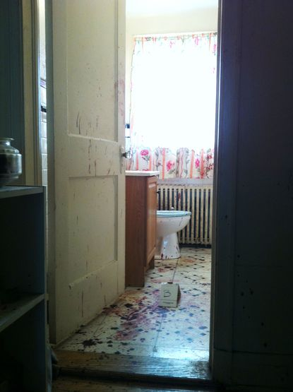 The bathroom of a home in the 5500 block of Lothian Road in Baltimore shows signs of a triple shooting Monday.