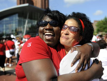 Robin Huger, left, and Deborah Sharpe, both of Baltimore County, greet each other at the 100th anniversary celebration of the Delta Sigma Theta sorority, which was held at the Inner Harbor.