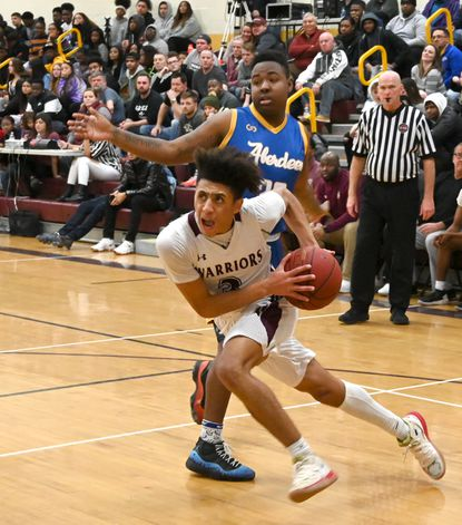 Havre de Grace's Gary Gibson gets by Aberdeen's Silas Jenkins and drives to the basket for a score during Friday night's game at Havre de Grace.