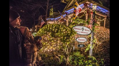 """Kristina Kramer of Bel Air with her chihuahua """"Lil Ricky Ricardo"""" and friend, Alex Walkings of Brooklyn, New York, admire the Christmas lights decorating the Spencer-Silver Mansion, during the 2018 Havre de Grace Candlelight Tour. This year's tour is scheduled for Dec. 12."""
