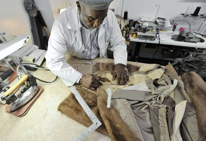 Seleh Rahman, furrier, tailor and designer, cuts a mink baseball jacket he is transforming into an a-line jacket. Rahman has operated his shop, Seleh's De Federal Hill, for over 22 years.