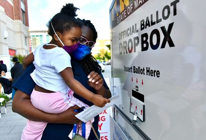 Early voting in Maryland will begin Oct. 26 and continue until Election Day. In this June 2, 2020, photo, Kelley Thorne, 3, helps her mother, Kinyel Snipes of Lansdowne, deposit her ballot in a drop box.