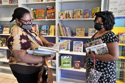 """Customers Erica Taylor, left, of Gardenville, and Kim Spears, a public school librarian, strike up a conversation at The Children's Bookstore while browsing for books Thursday. The store's owner, Melissa Doty, has decided to close the business for personal health reasons on July 25. Taylor, a regular customer, commented, """"It's such a loss because this store made space for everyone. I'm sad to see it go."""""""