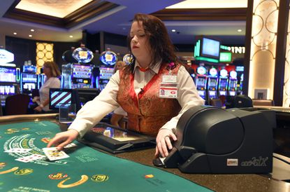 Kasey Thomas, a tables games dealer, uses a continuous shuffling machine, which speeds up blackjack games and makes it impossible for card counters to keep track of cards.