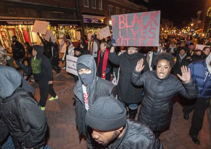 Demonstrators work their way up Main Street towards Lawyers Mall on Friday evening in Annapolis
