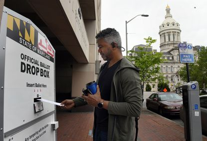 Jose Jimenez of Baltimore city places his ballot in a ballot box outside the city's Board of Elections office on the first day that drop boxes were available for voters.