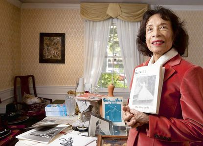 """Hazel Chung-Hood holds a Playbill from her Broadway performance in """"The King and I."""" Her studio and backyard were flooded by Tropical Storm Lee more than a month ago."""
