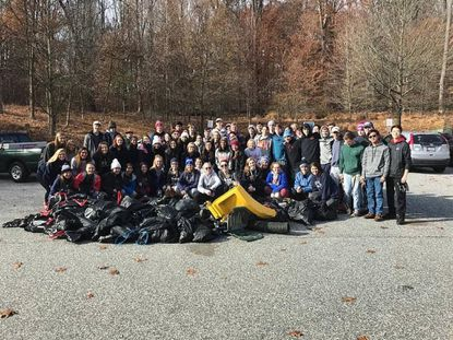 Students from Notre Dame Preparatory School and Calvert Hall College High School pose with some of their haul, which totaled about 400 pounds, from a Nov. 30 stream cleanup at Loch Raven. - Original Credit: Courtesy of Notre Dame Prep