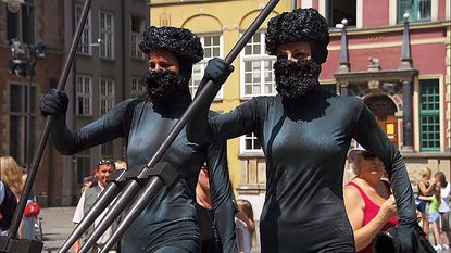 """In Detour A, Baseball wives Nicole (left) and Kim must dress and pose as a statue of Neptune on """"The Amazing Race."""""""