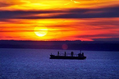 A freighter moves along the Chesapeake Bay during a sunset.