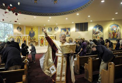 The Rev. Louis J. Noplos scatters flower petals among the congregation during the Holy Saturday Divine Liturgy at St. Saint Demetrios Greek Orthodox Church.