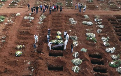 In this April 7, 2021 photo, cemetery workers wearing protective gear lower the coffin of a person who died from complications related to COVID-19 into a gravesite at the Vila Formosa cemetery in Sao Paulo, Brazil. Nations around the world set new records Thursday, April 8, for COVID-19 deaths and new coronavirus infections, and the disease surged even in some countries that have kept the virus in check. Brazil became just the third country, after the U.S. and Peru, to report a 24-hour tally of COVID-19 deaths exceeding 4,000. (AP Photo/Andre Penner, File)