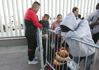 A young man (right ) rested his head on the barrier while waiting for their number to be called so they could be taken to the United States for their interviews on Friday, Sept.13, 2019 at the El Chaparral port of entry in Tijuana.