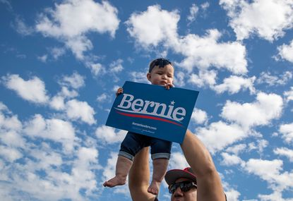 David Reyes holds up his baby, Galadriel Reyes, 8 months old, as they join supporters cheering a speech by Democratic presidential candidate Bernie Sanders at Valley High School in Santa Ana, California recently.