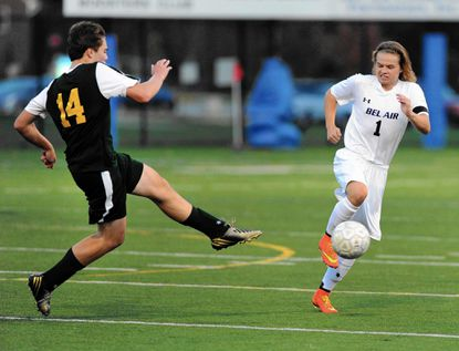 North Harford's Zach Fiacco sends the ball up the field as Bel Air's Drew Adams jumps to attempt the block during Tuesday night's boys soccer regional playoff game at Bel Air.
