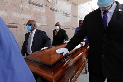 In this April 22, 2020, file photo, pallbearers, who were among only 10 allowed mourners, walk the casket for internment at the funeral for Larry Hammond, who died from the coronavirus, at Mount Olivet Cemetery in New Orleans. Hammond was Mardi Gras royalty, and would have had hundreds of people marching behind his casket in second-line parades. (AP Photo/Gerald Herbert, File)