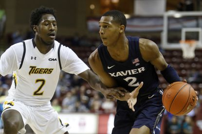 Xavier's Dahmir Bishop, at right, drives the ball over the defense of Towson's Allen Betrand in the second half of an NCAA college basketball game during the Charleston Classic Thursday, Nov. 21, 2019, in Charleston, SC. (AP Photo/Mic Smith)