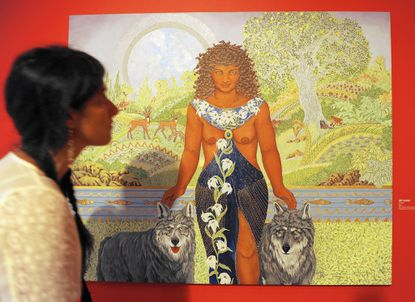 """A visitor walks by the painting """"Lilith"""" by artist Judy Tallwing at the American Visionary Art Museum, which is opening a new exhibit called """"The Visionary Experience Saint Francis to Finster."""""""