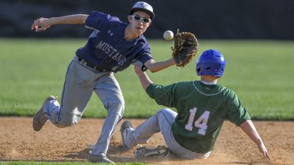 Marriotts Ridge's Karlyle Yarema flags down a throw to second as Atholton's Charlie Decelles slides in safely during a JV baseball game between Marriotts Ridge and Atholton on May 6.
