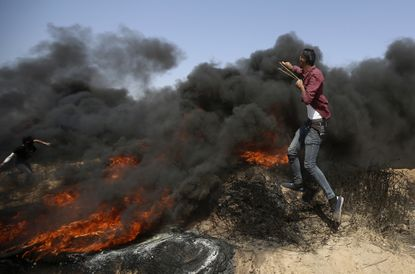 Palestinians hurl stones and burn tires near the fence of the Gaza Strip's border with Israel, during a protest east of Khan Younis, in the Gaza Strip, June 8, 2018.