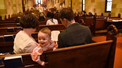 Nine-month-old Elizabeth Ruth Leigh with her parents, Laura Yoder and John Leigh of Charles Village, during the Sunday service at St. John's Episcopal Church in the Village, which is fighting a proposed closure by the Episcopal Diocese of Maryland.