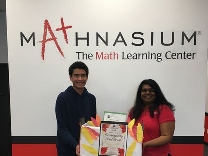 Gabriel Atalla, 15, alongside Surani Peiris, center director of Mathnasium in Sykesville, drops off one of the collection boxes at Mathnasium for Macbeth Academy's food drive.
