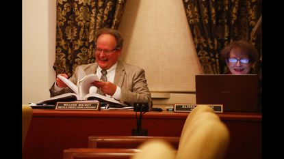 Bill Mackey, who left his position as Westminster's director of community planning and development on Friday, flips through the city code at a Common Council meeting in November.