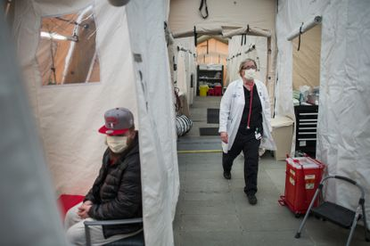 A flu patient awaits treatment in a surge tent outside the emergency room of Lehigh Valley Hospital in Allentown, Pennsylvania, on Jan. 30, 2018. Even a mild flu season could stagger hospitals already coping with COVID-19 cases.
