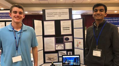 Alex Ozbolt, left, and Varun Singhai, seniors at Dulaney High School, stand by their Baltimore Science Fair project, which took first place in the high school division from the American Society for Quality, and third place from the U.S. Public Health Service, among other honors.