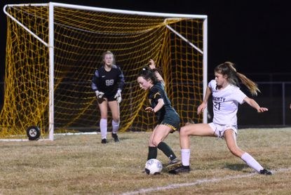 Century's Haley Greenwade, left, gets past Liberty's Erin Mulholland before sending a shot towards the goal and keeper Lauren Mondor during a girls soccer game at Century High School on Thursday, March 11, 2021.