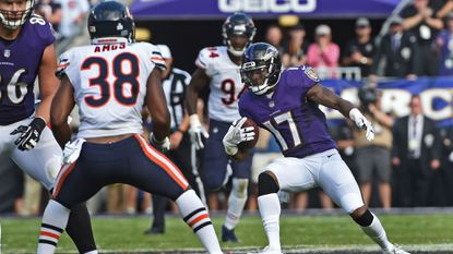 Ravens wide receiver Mike Wallace, right, looks for running room against the Bears after a catch in the fourth quarter last Sunday.