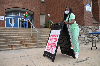 Principal Shandra Worthy-Ownes carries out a sign to remind students to social distance when coming into the building for summer school at Bernard Harris Elementary School in Baltimore in July. Some say Baltimore schools should also find a way to reopen now.