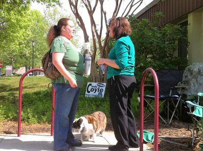 CA board member Cynthia Coyle, right, talks with Ruishella Sellers outside the Harper's Choice polling place Saturday as Coyle's dog, Owain, looks on. Coyle was elected to another two-year term in the only contested CA board race.