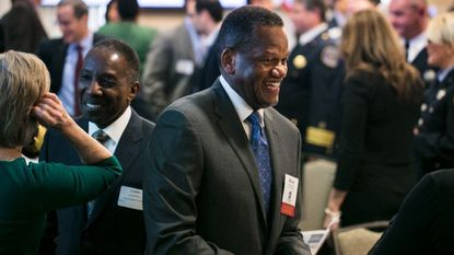Columbia Association President Milton Matthews talks with others during the opening networking hour of the State of the County address for newly elected Howard County Executive Calvin Ball.