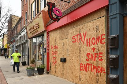 """Diablo Doughnuts on S. Light Street in Federal Hill is boarded up. The message on the plywood reads: """"Be Open Soon"""" and """"Stay Home + Safe Baltimore."""" Some businesses closed due to the coronavirus restrictions are now boarded up. March 31, 2020"""