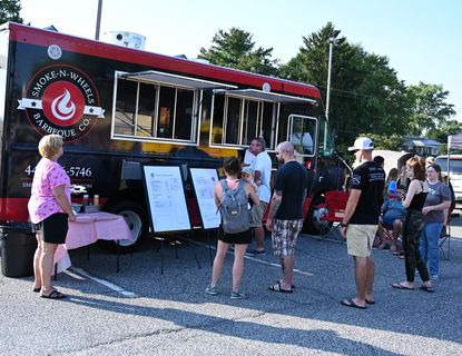 Folks look over the menu at the Smoke-N-Wheels Barbeque Company truck during the Fallston Volunteer Fire Company's Food Truck Thursdays event at their station on Carrs Mill Road Thursday evening.